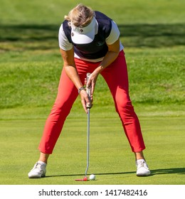 Braunschweig, Germany, May 18., 2019: Woman in red trousers with spread legs, an umbrella cap and a golf club standing in the middle over the golf ball to putt it into the target.