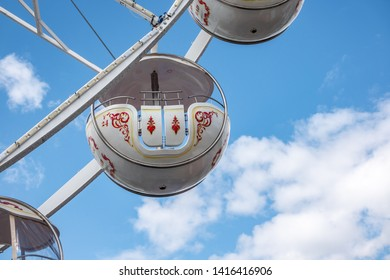 Braunschweig, Germany, May 5., 2019: Gondola of a giant wheel with white struts and white gondolas in front of a summery white-blue sky