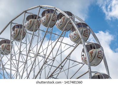 Braunschweig, Germany, May 5., 2019: Ferris wheel with white struts and white gondolas in front of a summery white-blue sky