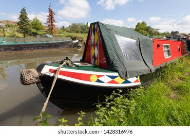 Braunston, Northamptonshire / UK - Mat 21st 2019: Brightly painted narrowboat with a diamond design is moored against the bank of the Grand Union Canal. On the opposite bank is a boat used for cargo.