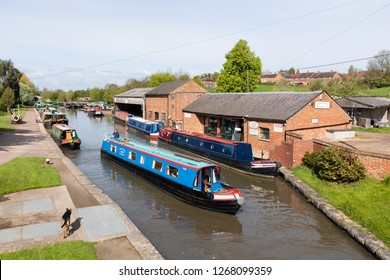 Braunstone, Northamptonshire / UK - May 3rd 2018: Elevated viewpoint shows a blue narrowboat sailing on a canal. Boats are moored on either side of the canal and a dog is walking on the towpath.