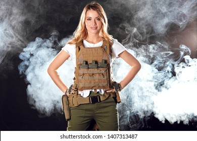 Brave amazing army girl wearing military plate carrier upon white t-shirt. Female ranger posing isolated on black studio background