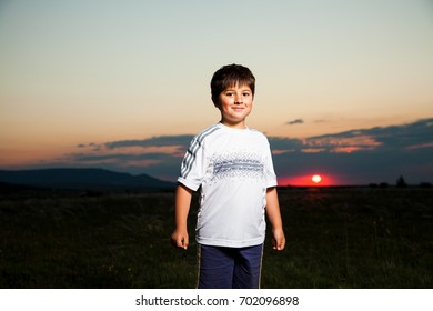 Brave boy is smiling against the dusk with sun