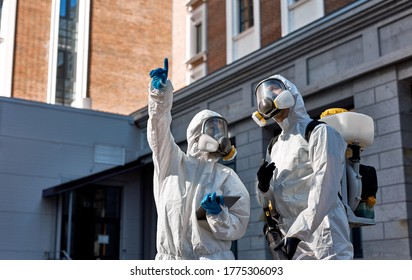 brave caucasian cleaning service workers in biosecurity suit, mask and gloves, carries out disinfection from Coronavirus, use tablet, discuss, work as a team
