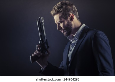 Brave cool man holding a dangerous weapon on dark background