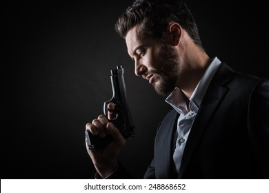 Brave cool man holding a gun on dark background