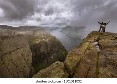 A brave courageous couple in love is standing at the edge of the dangerous Pulpit cliff on the fjords of Norway, despite the bad weather with a strong wind and rain surrounded by low clouds.