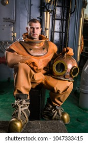 a brave diver in gear sits on the deck of a ship