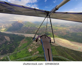 Brave extreme hang glider pilot flies high over valley with river and mountains in Gemona, Italy