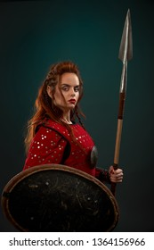 Brave female warrior wearing in red medieval costume looking at camera, holding shield and big spear. Beautiful, gorgeous woman with long ginger hair posing in studio with solid background.
