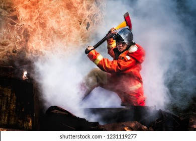 Brave fire man climb on car crash accident with axe for rescue victim life on fire and thick smoke area