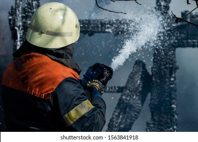 Brave firefighter saving burning building. Firefighter work concept. Firefighter are using water in fire fighting operation. Real brave hero combat the fire with foam extinguisher