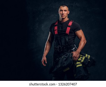 A brave fireman holding a jacket and looking at a camera. Studio photo against a dark textured wall