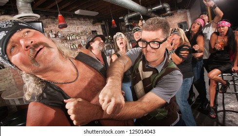 Brave geek with glasses punches biker gang man in bar