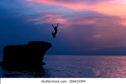 Brave girl jumping from the rocks in the evening on beautiful purple sunset background, summer adventure, freedom concept
