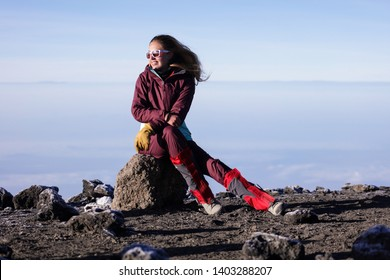 Brave girl sitting on the rock on the top of the mountain. Cold wind blowing in a face, sunglases on the face, long hair. Wearing warm sport wear, jacket, boots. Climbing for couple days. Clouds