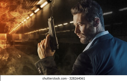 Brave handsome hero agent holding a gun and walking into the fire in an underground tunnel, danger and crime concept