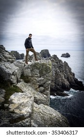 A brave handsome men tourist, resisting strong winds and standing on the high dangerous cliff near the atlantic ocean deep water, Brittany in France.
