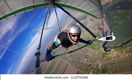 Brave hang glider pilot soar high over terrain. Selfie shot of extreme sport with action camera