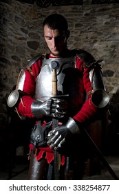 Brave Knight Standing With Head Bowed in Prayer and Holding Metal Sword Against Old Stone Wall