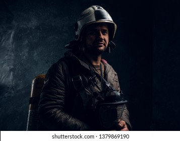 Brave lifeguard with helmet and oxygen mask in hands. His face is in shadow. There are dark background.