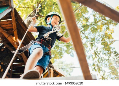 brave little boy having fun at adventure park and smiling to camera wearing helmet. toddler climbing in a rope playground structure. Scout practicing rappelling