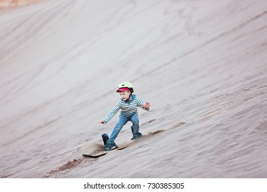 brave little boy sandboarding in valle de la muerte in atacama desert, chile, active healthy lifestyle concept