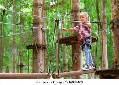 Brave little child in safety harness climb on tree tops route to zip line, pass hanging bridge obstacle in adventure rope park. Outdoor activity, family lifestyle in summer camp on vacation with kid