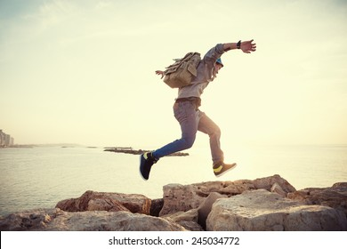 brave man with backpack running over rocks near ocean in sunset