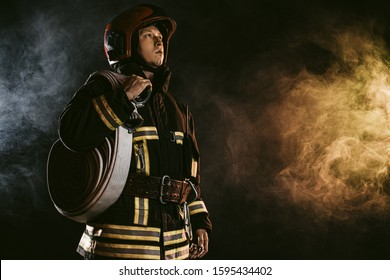brave man fire fighter extinguishing fire, work at fire station and doing his work wearing protective uniform