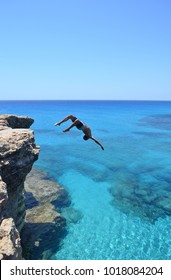 Brave man jumping off cliff into the Mediterranean Sea.