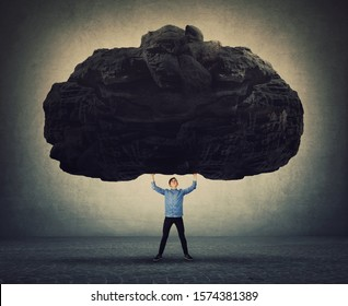Brave man making effort facing life problems as holding a huge boulder about to squeeze him. Difficult task, guy convinced in his powers, standing up to troubles. Super strength, burden concept.