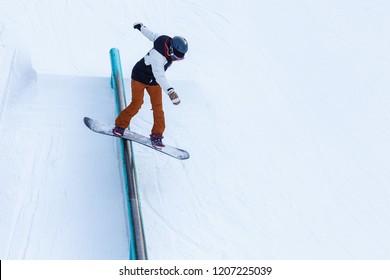 A brave man performs a rail slide on snowboard