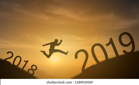 brave man successful concept,silhouette man jumping over the sun between gap of the mountain from 2018 to 2019 new year , it feel like a winner, success, finish,reach a goal of live, jobs,