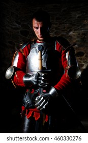 Brave Medieval Knight Standing With Head Bowed In Prayer And Holding Metal Sword Against Old Stone Wall, Vivid Colors
