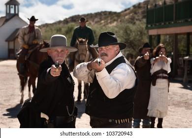 Brave men aim their guns in old west town