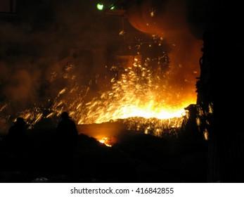 Brave men in metal fire sparks. Workers makes liquid metal in blast furnace.