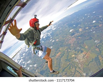Brave Parachutist with red helmet jump out of the plane