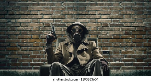 Brave post apocalyptic survivor with gas mask and gun: environmental disaster, crime and chemical warfare concept