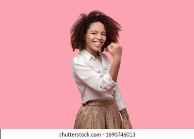 Brave, self-confident. Beautiful young woman of african appearance, with a tattoo, showing a strong fist, looking forward, laughing, confident.