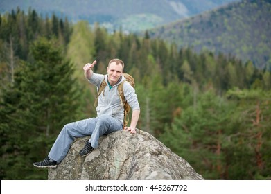 Brave smiling guy with a backpack sitting on the peak of a rock and showing thumb up gesture of good class, with an astonishing blurred view on forest valley and hills