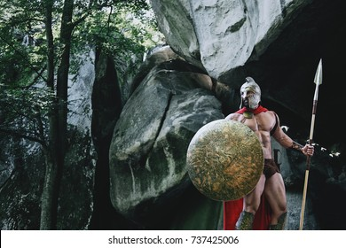 Brave Spartan warrior wandering in the woods walking with his weapon holding a spear and a shield.