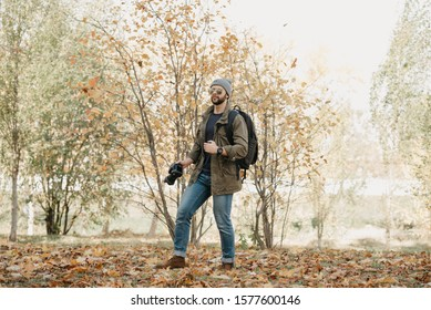 A brave traveler with a beard in aviator sunglasses with mirror lenses, olive military jacket, jeans and shirt with wristwatch holds the DSLR camera, looks around near the meadow in the forest