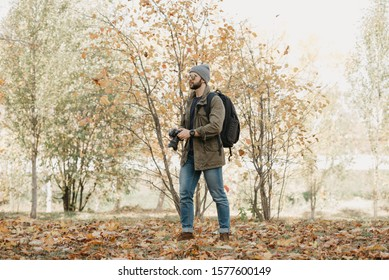 A brave traveler with a beard in aviator sunglasses with mirror lenses, olive military jacket, jeans and shirt with wristwatch holds the DSLR camera, looks around near the meadow in the wild forest