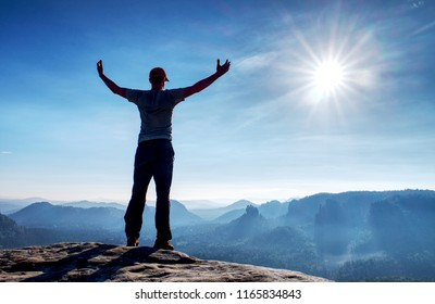 Brave traveler man raised hands. Alone traveling in rocks, hiker stand on cliff mountain. The active lifestyle weekend.