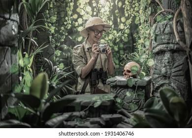 Mutige Frau, die den Dschungel erforscht und mit ihrer Kamera Fotos macht, findet sie alte Ruinen und einen menschlichen Schädel