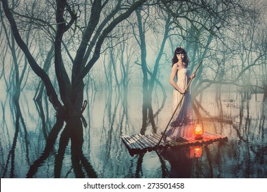 Brave woman in fairy forest foggy floats on a raft with a lantern. Alone girl looking for a way in the dark.
