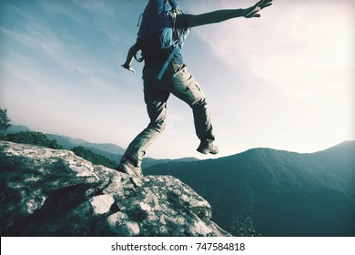 brave woman hiker walking to the cliff edge on mountain top
