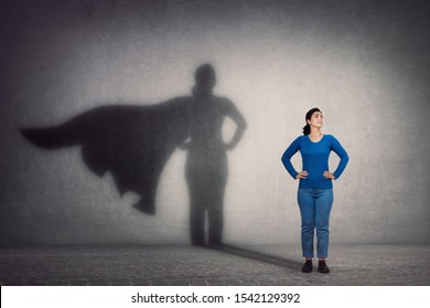 Brave woman keeps arms on hips, smiling confident, casting a superhero with cape shadow on the wall. Ambition and business success concept. Leadership hero power, motivation and inner strength symbol.