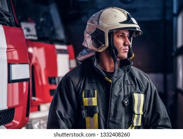 Brave young fireman wearing protective uniform standing next to a fire engine in a garage of a fire department and looking outside